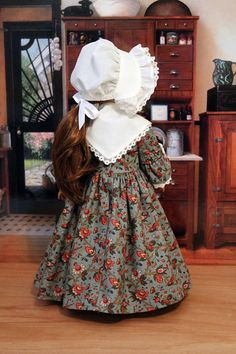Felicity is wearing a fall Colonial dress made from a Keepers Dolly Duds pattern The fabric is a quilters cotton print in fall colors of green and rust. The sleeves have a double ruffle with fabric and lace. The fichu is also trimmed with lace. The lined bodice and sleeves feature ruching and the neckline has a white ruffle. It has a full gathered skirt. The dress closes in the back with buttons. The mob cap is made from ivory batiste. The seams are serged for a professional finish. Doll…