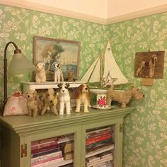 Dog figurines, a vintage lamp and artworks of dogs make a charming vignette. The fact that it's on top of a green-painted bookcase makes me like it even more.