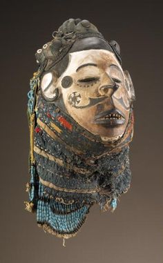 Africa | Face maks. Igbo peoples. Nigeria | Early - mid 20th century | Wood, textile, plant fiber, glass beads, metal, buttons, kaolin, encrustation | When worn with an appliquéd and embroidered fitted cloth costume, this face mask, with its elaborate coiffure and even features, transformed a male dancer into the ideal Igbo woman: someone who is both beautiful and good.