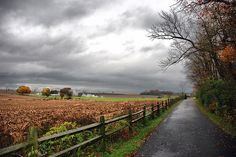 The country side with storm clouds and a fence