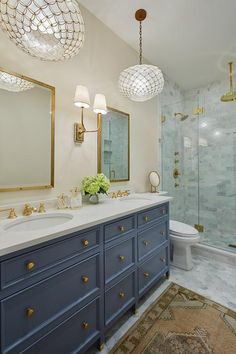This elegant bathroom features a Hulton Double Sconce mounted between Restoration Hardware Industrial Rivet Mirrors hung above a blue dual washstand accented with brass knobs and a white quartz countertop finished with antique brass faucets.