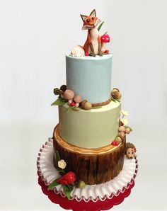 """Rustic Woodland Animals Cake - This was a birthday cake made for my sweet daughter's 8th birthday.  She wanted a """"camping"""" party, but it still needed to be girly.  So we designed her party to be a woodland theme with sweet little animals.  The cake was inspired by her invitations, and was complete with a tree slice, cute hedgehog, toadstools, ferns, mushrooms, and a darling little fox."""