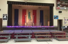 Red, white and blue backdrop created with plastic tablecloth rolls; they were attached under the lay in ceiling and hung vertically in strips. What you see is the actual width of the tablecloth. Columns belong to the school, and were decorated with patriotic bunting from Oriental Trading. See separate post about the Statue of Liberty and the lighted garland across the stage.