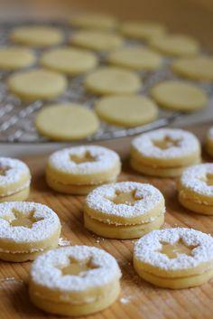 Endspurt in der Weihnachtsbäckerei! Bei der ganzen Lebkuchen-Dominanz muss es auch noch etwas Fruchtiges geben. Dieses Rezept kam wie gerufen, denn zufällig stand im Keller noch ein importiertes Glas Lemon Curd. Neben der Füllung schmeckt aber auch der Teig wunderbar zitronig durch frische Zitronenschale und -saft. Das Ergebnis: Unglaublich mürbe Plätzchen, die im wahrsten Sinne des Wortes