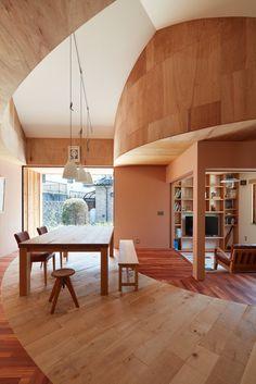 広島市郊外の住宅街に建つ平屋の住まいです。 建築主は仕事の引退を機会に、畑として利用していた土地に、老後の住まいを建てることに。 住まいの希望としては、夫婦2人が暮らせ、植栽を育てることを楽しめる家としたい。 将来雑貨屋にもなり、ギャラリーやワークショップができる大きな空間があり、大きなテーブルを家の真ん中に置きたい、ということでした。 そのような希望から、住まいの外に並木道がある家を提案しました。 建物の外に、家と繋がる幅広い土間をつくり、その土間の中や周囲に草花や木を植えることで、小さな並木道がある住まいです。 並木道は住まいと円形に繋がっています。 また、元々あったミモザの木に愛着があるとのことで、それを生かした計画としています。 敷地の道路側に広がる眺望、南面からの採光と、隣地からのプライバシーのバランスを考え、建物配置を少し斜めに配置しています。 人が集まることを考え、キッチンはオープンに。 書斎も建具を開けるとリビングダイニングと一体になり、広く使えるようになっています。 建築後、近くに住む建築主の父や母、お子さんなど、皆が集う家となっているそうです。…
