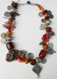 Berber necklace with coral beads, resin amber beads, some glass beads, little shells, silver coins, silver and metal beads and objects. It's approx. 70 years old. One string with three short pieces of 3 strings between. | 450 Euro