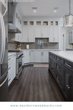 White Shaker Kitchen Cabinets with dark kitchen island and stainless steel appliances White Shaker Cabinets, White Kitchen Cabinets, Kitchen Shelves, Kitchen Island, Shaker Doors, Shaker Style Cabinets, White Appliance Kitchen, Upper Cabinets, Oak Cabinets