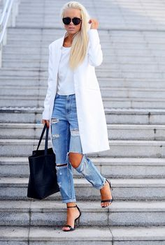 Девушка в белом пальто и рваных джинсах