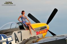 A model sits aft of the engine of a P-51 Mustang fighter plane.