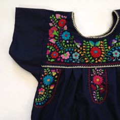 These Mexican hand-embroidered dresses come from Puebla. They are sewn of a nice cotton blend (poplin) that is vibrantly colored and the gorgeous, colorful hand-done embroidery is unique to each piece