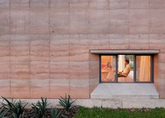 Rammed earth walls with striated patterns frame this house in Mexico.
