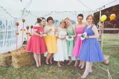 Bridesmaids wearing vintage retro 1950s different coloured bespoke  dresses - Image by Sasha Weddings - Bride wears a lace tea length dress for a brightly coloured vintage inspired wedding with DIY brooch bouquets, lego buttonholes, a swing boat & garden games.