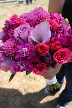 Bridal bouquet of lavender mini calla lilies, lavender roses, magenta stock, purple tulips, hot pink spray roses, and bright pink dahlias.