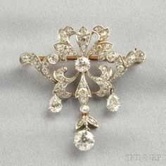 Edwardian Diamond Pendant/Brooch, the scrolling foliate form suspending an old European-cut diamond weighing approx. 0.90 cts., and old pear-shape diamonds, further set with old European- and old mine-cut diamonds, platinum-topped 18kt gold mount, lg. 1 1/2 in.