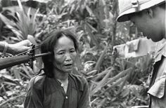 A female Viet Cong suspect is questioned at gunpoint by a South Vietnamese national police officer at Tam Ky, about 350 miles north of Saigon, November 1967. The M-16 rifle was held by a U.S. soldier during an operation of the 101st Airborne Brigade, searching villages of the coastal plains for suspected Viet Cong enclaves