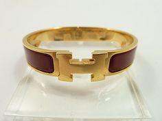 333aa7d3c112 HERMES   Bracelet rigide ouvrant en métal doré laqué bordeaux, le fermoir  composé de la