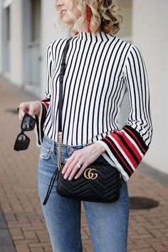 Straight leg mom jeans, striped bell sleeve top, black Gucci marmont bag, black sunglasses, curled blond bob, red statement earrings
