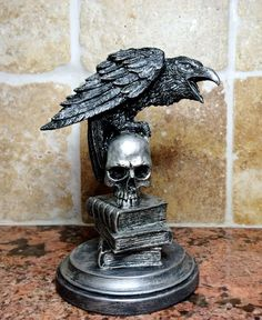 """Raven Statue By: Dellamorte & Co. 6"""" tall sculpture of a raven perched on a skull and stack of books, evoking the poem by Edgar Allan Poe. Cast in resin and hand painted *Made to order, please allow a 2-3 weeks for shipping*"""