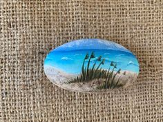 """This hand painted beach rock has a sand dune beach scene with beach grass and ocean waves. The back of the rock is painted white so you can add a personalized message if you want. Approximate Size: 3"""" x 1 1/2"""" We use professional grade high quality acrylic paints and spray the finished rock with a Ceramic Painting, Stone Painting, Rock Painting, Painted Rocks, Hand Painted, Beach Grass, Beach Rocks, Rock Design, Driftwood Art"""