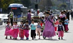 "Children wearing traditional costume ""Hanbok"" walk together hand in hand."