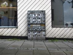 This street artist turns urban infrastructure into miniature apartment buildings
