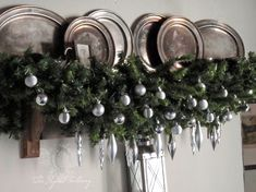 Old pewter plates, pine evergreen swag and silver baubles, some shiny, some mat. Image by The Paper Mulberry