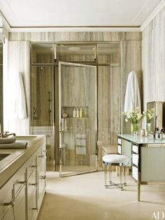 The walls in the master bath of this Manhattan penthouse by interior designer Delphine Krakoff and architect Mark Ferguson are clad in silver travertine from Walker Zanger; the 1930s vanity stool by Samuel Marx is from Alan Moss | archdigest.com