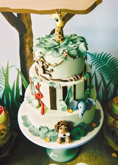 "combine junkle decor for ""Wild One"" first birthday jungle cake with a fondant giraffe topper"