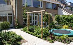 Speelplek met schommel en trampoline, mooi verwerkt in tuinplan