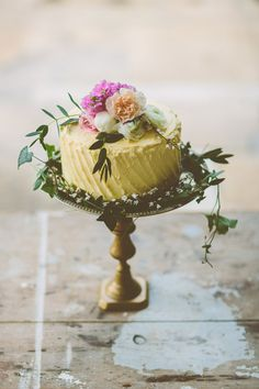 pale yellow lemon wedding cake with flower cake topper on brass cake stand