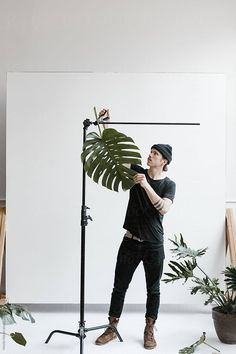 young man setting up plant props in photo studio by Nicole Mason for Stocksy Uni. - Photography, Landscape photography, Photography tips Photography Studio Setup, Photography Lighting Setup, Creative Photography, Amazing Photography, Photography Tips, Photography Business, Photography Colleges, Photography Hashtags, Photography Outfits