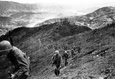 Men of the 9th Infantry Regiment climb a steep slope on Bloody Ridge