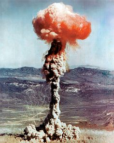 Charlie | Oct 30, 1951 | The red/orange color seen here in the cap of the mushroom cloud is largely due to the ionization of air molecules, predominantly produced by the preceding fireball's intense heat in combination with the oxygen and nitrogen naturally found in air. Oxygen and nitrogen, though generally nonreactive toward each other, form NOx species when heated, specifically nitrogen dioxide, which are largely responsible for the red/orange color.