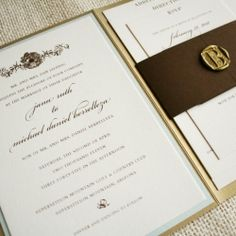 Old world style wedding invitations in a beautiful gold enclosure.