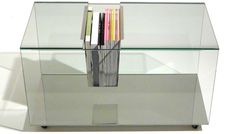 Mesa composta de tampos e laterais em vidro incolor com base em inox com rodízios. Entre os tampos, um suporte em inox para acomodar livros e revistas.