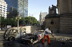 A municipal worker sweeps the streets by two cars destroyed the previous night by demonstrators in downtown Rio de Janeiro, Brazil on June 18. Rio police fired tear gas and rubber bullets in clashes with protesting youths early Tuesday, after tens of thousands rallied in major Brazilian cities against the huge costs of hosting the 2014 World Cup.