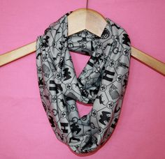 Infinity scarf featuring Game of Thrones figures. Gray background with black crests. This is an ideal way to show your loyalty to the Game of
