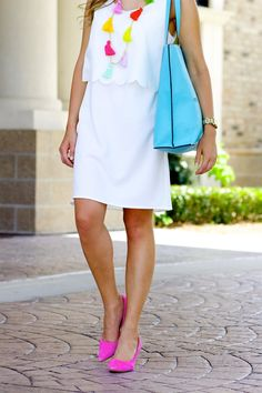 White scallop dress with pops of fuchsia and a multi colored tassel necklace