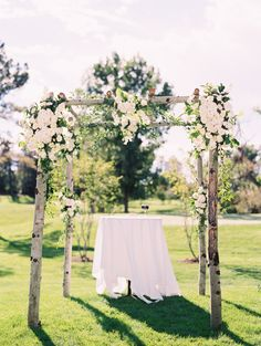 Simple Outdoor Ceremony Structure with masses of white flowers -- See more on http://www.StyleMePretty.com/2014/03/31/colorful-outdoor-celebration-after-the-storm/ Photography: Sara Hasstedt - sarahasstedt.com #smp