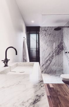 bathroom with marble, natural wood and black faucets