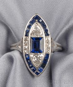 Art Deco Platinum, Sapphire, and Diamond Ring, of navette form, set with a rectangular-cut sapphire, with shield-shape diamonds, with calibre-cut sapphire and fancy-cut diamond edges