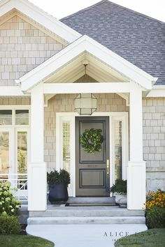 Suzanne Kasler Morris Lantern Ed Above A Black Front Door In Covered Porch With Border Doormat And Styled Potted Plants