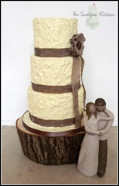 3 tier rustic butter-creamed wedding cake with a hessian style ribbon trim and handmade ribbon flower complimented by a choice of 2 stunning Willow tree keepsake figurines and displayed on a solid wooden tree stand x