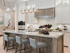 The kitchen in this home is the cornerstone of the floor plan, creating open sight lines to the pool and outdoor living areas. Complementary finishes and beautiful design are everywhere you look, from the two-inch mitered Sea Pearl quartzite used as the island countertop to the Alabaster white and driftwood-colored floor to ceiling cabinetry by Ruffino Custom Cabinetry.