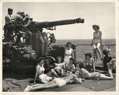 1945- Group of U.S. Army nurses sunbathe beside a 4mm anti-aircraft gun and its crew aboard a Coast Guard-manned troop transport returning to the states.