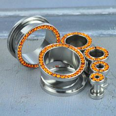 316L stainless surgical steel externally threaded eyelet with orange press fit CZ gems Quantity: sold as 1 pair (2 pieces) Style: round eyelet, 2 flat sides - 1 side gemmed Flare: double flare, back f