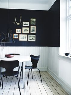 Dining area with walls painted only half. Gives a cool and calm feeling, and together with the gallery wall gives a masculine look.