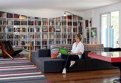 No sofá com almofadas de Adriana Barra, a moradora Dedéia Meirelles aproveita o novo apê. Ao fundo, a grande estante Treme-Treme, do coletivo Triptyque, guarda e exibe livros