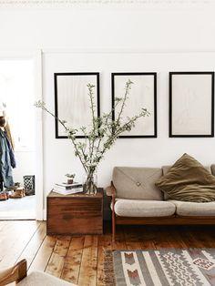 drewniane deski podłogowe + szary dywan + beżowa sofa + białe ściany + czarne ramki