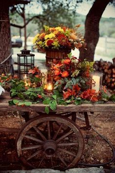 An old wagon converted into a rustic makeshift wedding display. To decorate use old lanterns and bright orange and red flowers for an amazing rustic Fall decor.